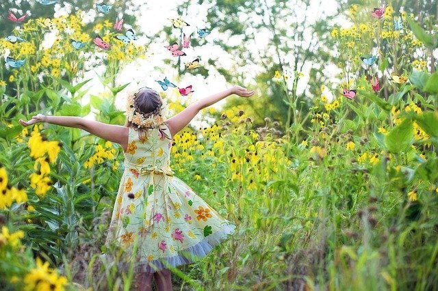 Happy girl in a flower meadow. Gardening For Better Health And Wellbeing