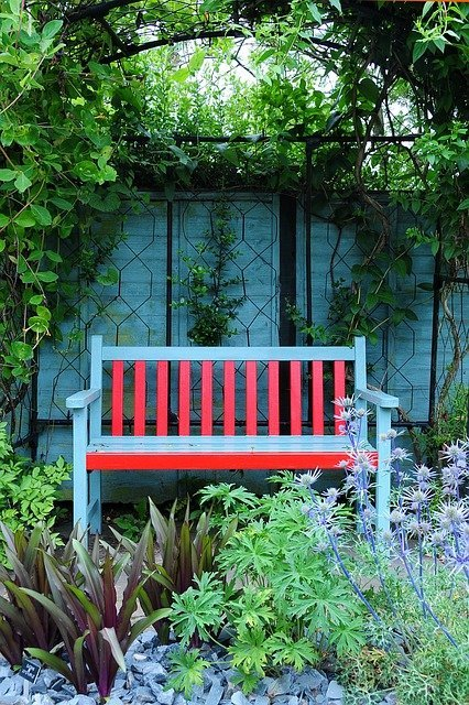 Blue and red bench with a blue fence in a garden.